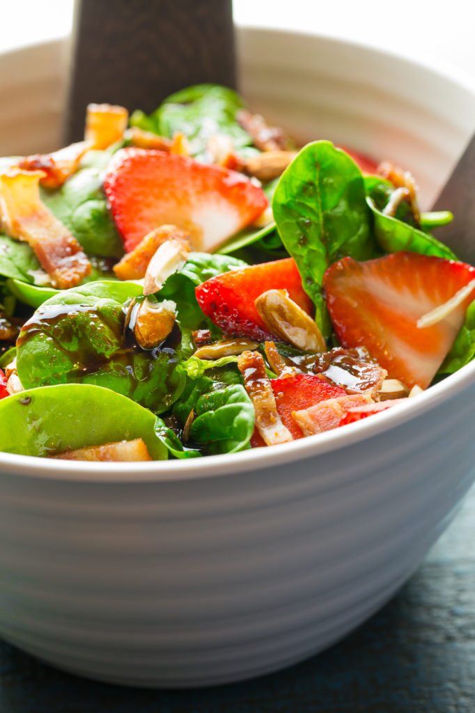 Simple spinach salad in a white bowl