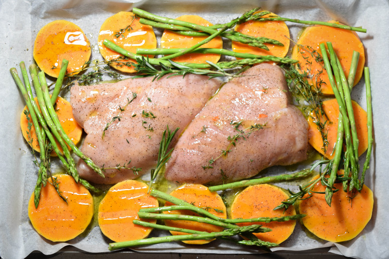 Raw turkey tenderloins with asparagus and butternut squash