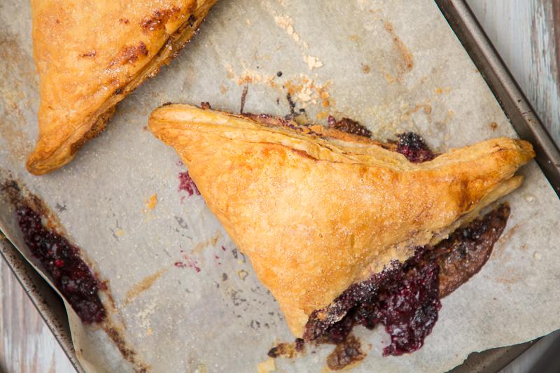 blue raspberry cheesecake turnovers on a baking sheet
