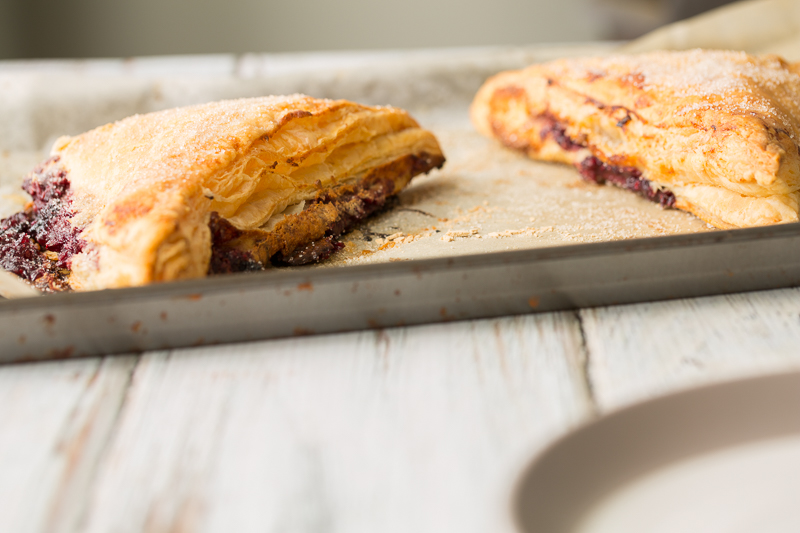 blue raspberry cheesecake turnovers on baking sheet