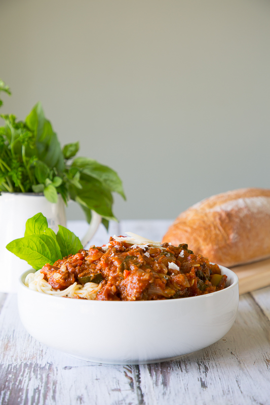 large bowl of spaghetti with bread and herbs in background