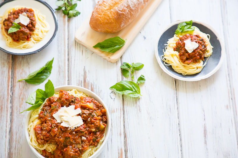 Plates of spaghetti sauce and pasta with rustic loaf of bread