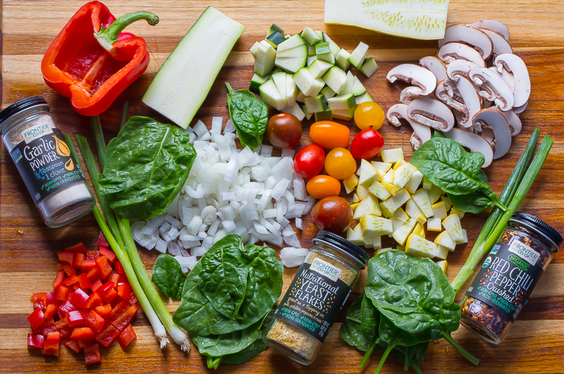 Fresh produce and spices on teak cutting board