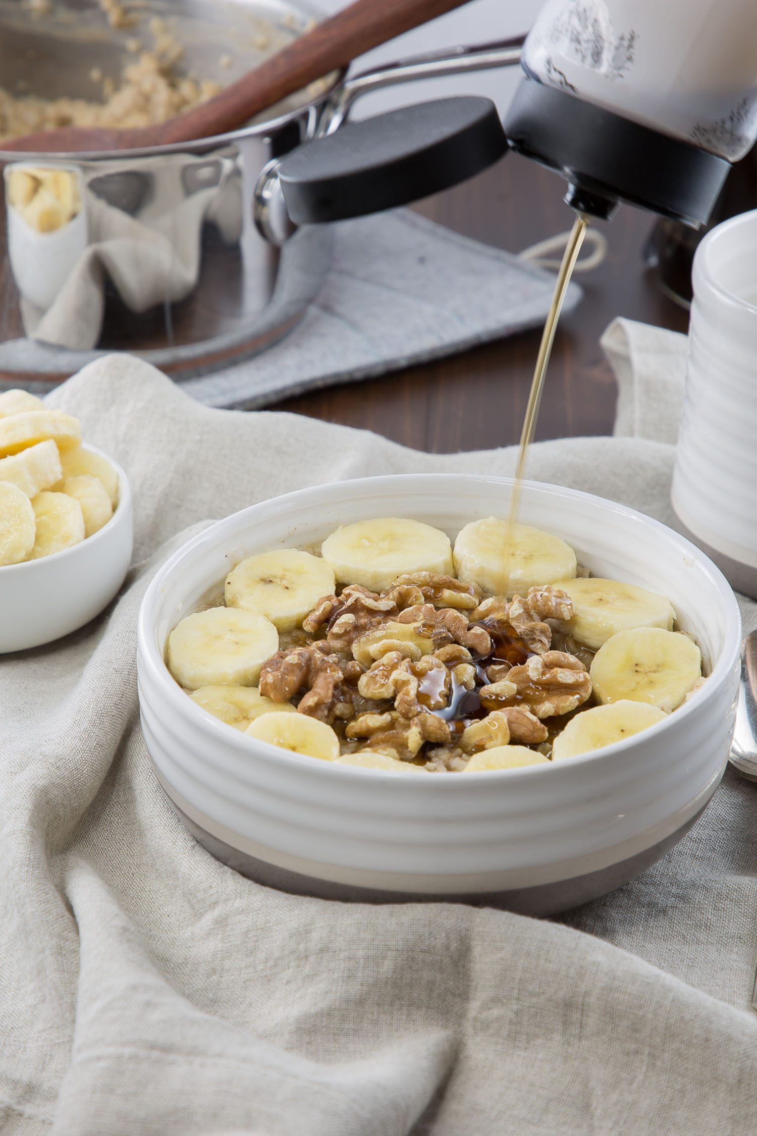 banana nut oatmeal with maple syrup pouring on it