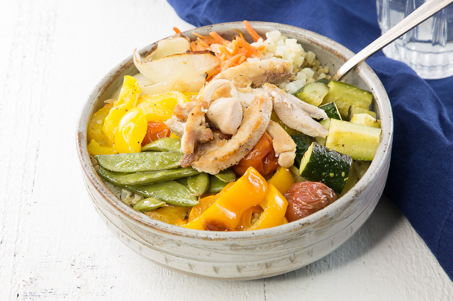 close up of roasted chicken and veggies in a rice bowl