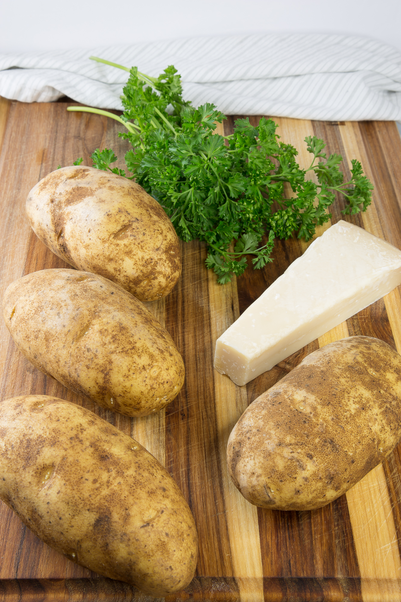 russet potatoes, parsley, and parm on a cutting board