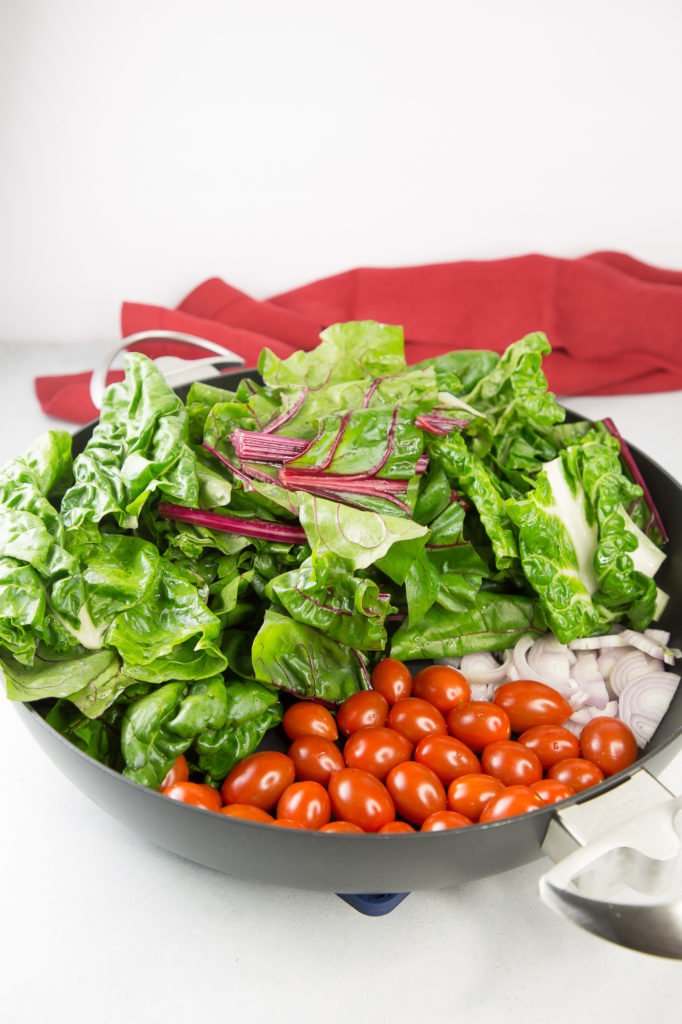 Chard, tomatoes, and shallots in a chef pan