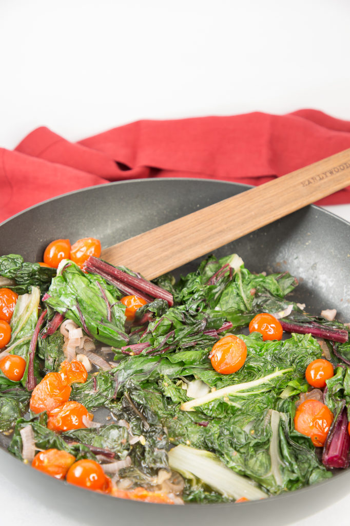 Sautéed chard, shallots, and tomatoes in a chef pan