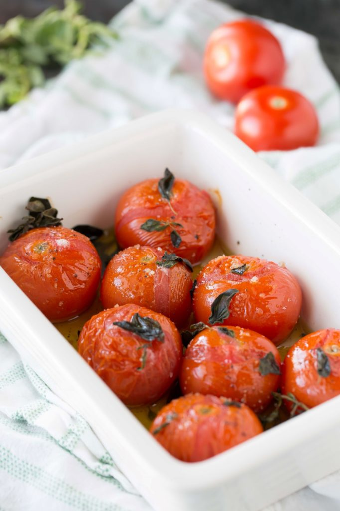 broiled tomatoes with fresh oregano in baking dish
